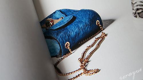 青い革にゴールドチェーンのバッグ